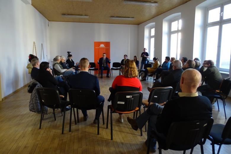 Ludzie siedzą w kregu. W tle - pomarańczowyczowy banner RPO, z przodu - kobieta w pomarańczowym swetrze