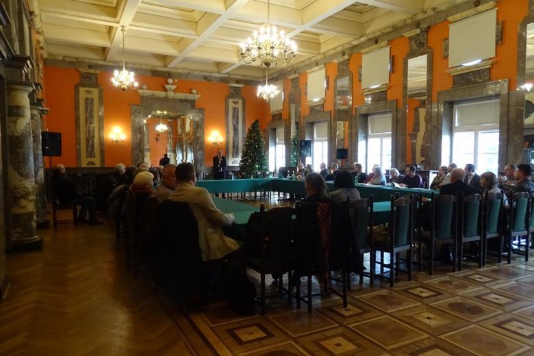 Grupa ludzi przy stołach ustawionych w czworokąt w zabytkowej sali