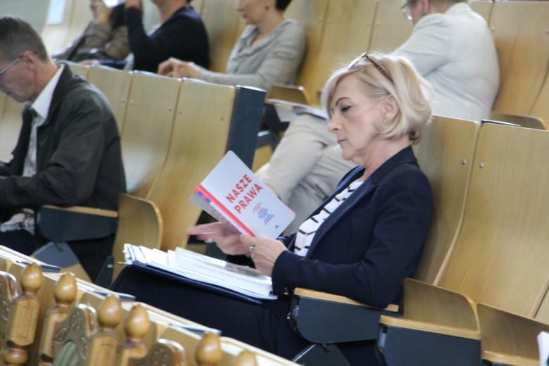 Kobieta na widowni trzyma w ręku publikację pod tytułem Nasze prawa