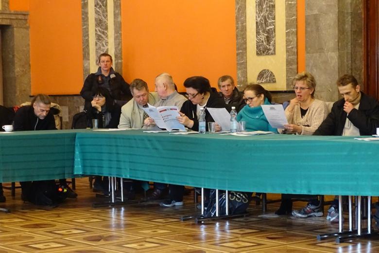 Ludzie siedzą przy stole i preglądaja materały informacyjne RPO