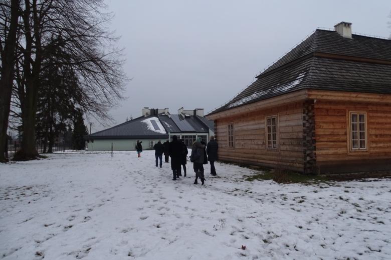 Drewniany dworek i nowoczesny budynek, ludzie