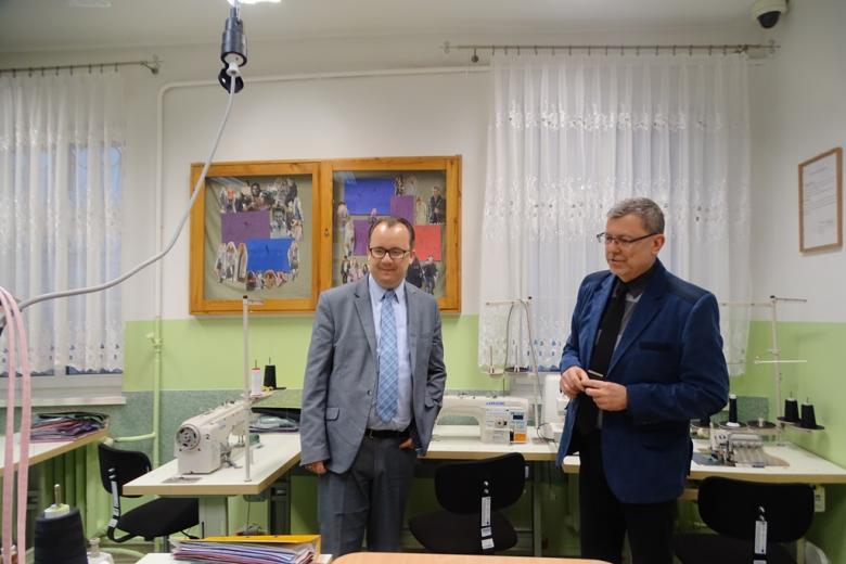 Dwaj mężczyźni w sali, gdie na stolikach stoją maszyny do szycia