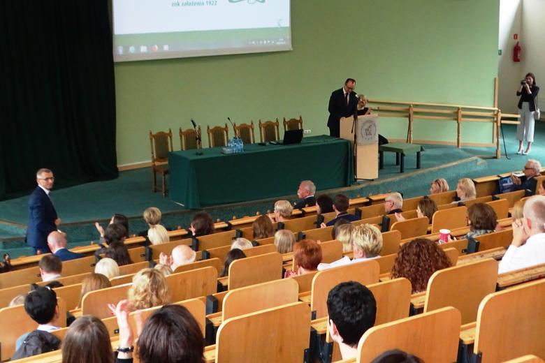 Sala plenarna, mężczyzna przy mównicy, w pierwszym rzędzie stoi i wita zebranych inny mężczyzna