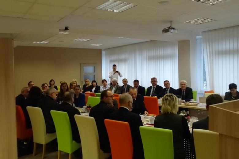 Ludze na sali konferencyjnej pomaranczowe i zielone krzesła