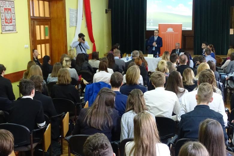 Aula szkolna, w której siedzą młodzi ludzie