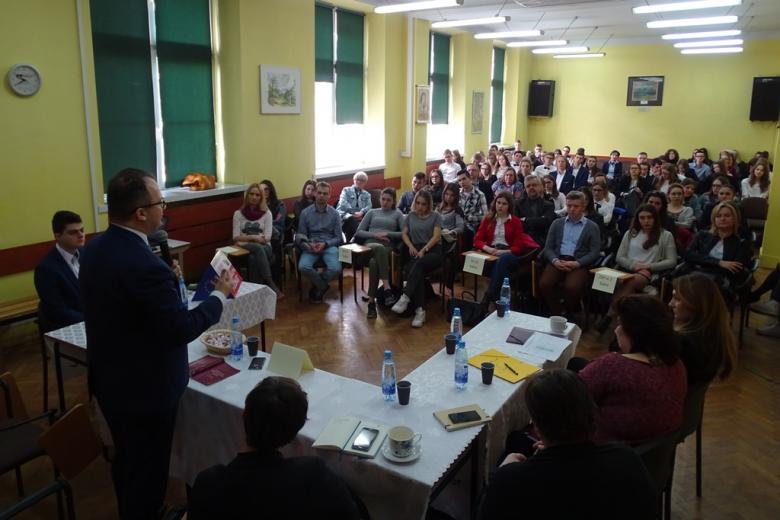 Młodzie ludzie w auli słuchają wykładu