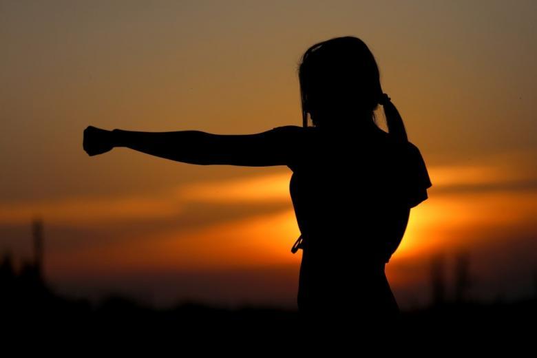 Kobieta z wyciągniętą ręką o zaciśniętej pięści (ruch karate) na tle zachodzącego słońca