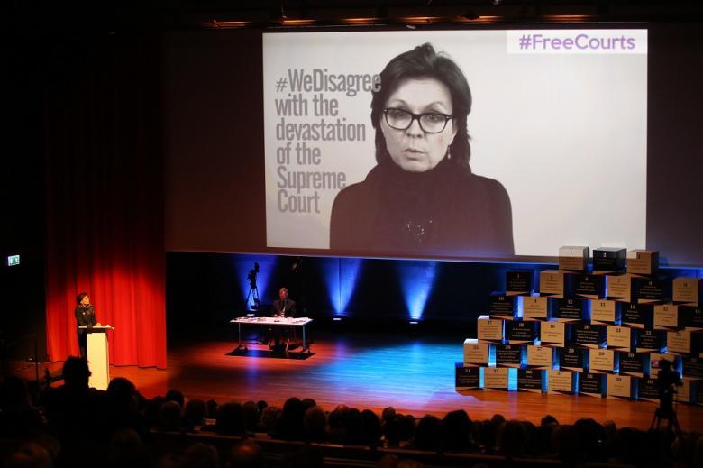 """Kobieta przy mówinicy, na ekranie wielki jej wizerunek i napis po angielsku """"Wolne sądy"""""""