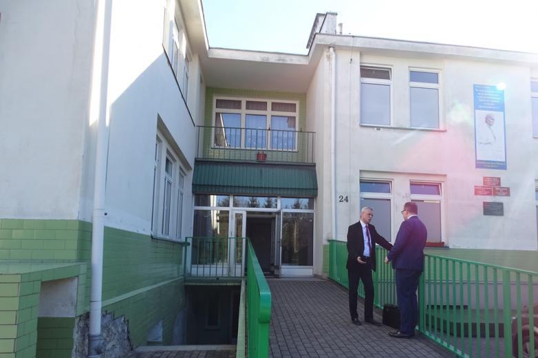 Dwaj mężczyźni rozmawiaja na schodach przed budynkiem