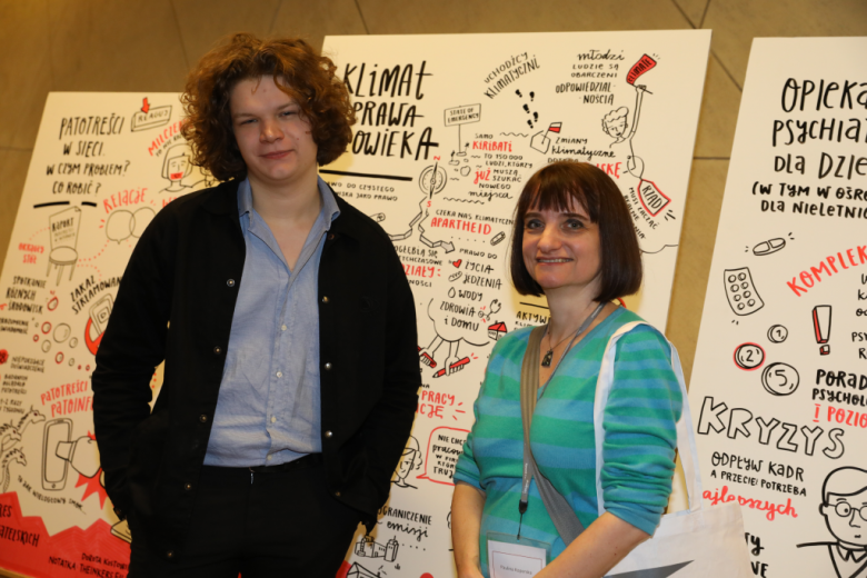 Kobieta i mężczyzna pozują koło grafiki Klimat i prawa człowieka