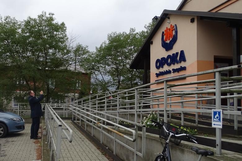 Zdjecie: mężczyzna robi zdjęcie budynkowi z napisem Spółdzielnia Socjalna OPOKA, z podjazdem dla osób na wózkach