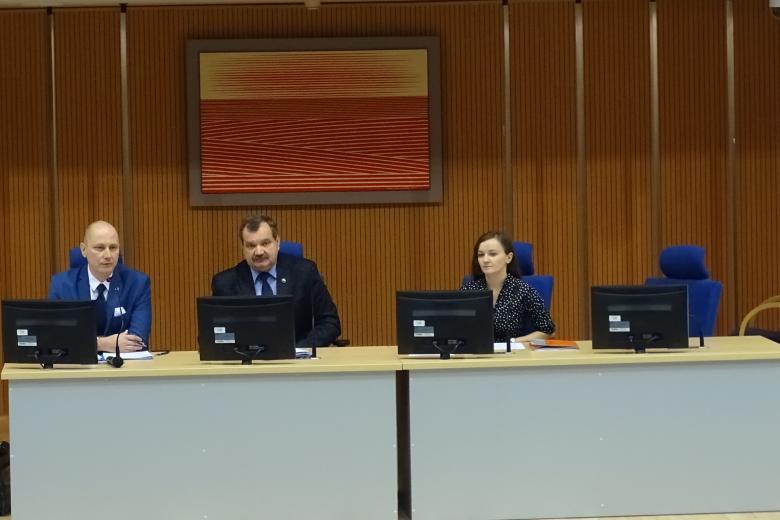 Zdjęcie: dwaj mężczyźni i kobieta za stolem prezydialnym