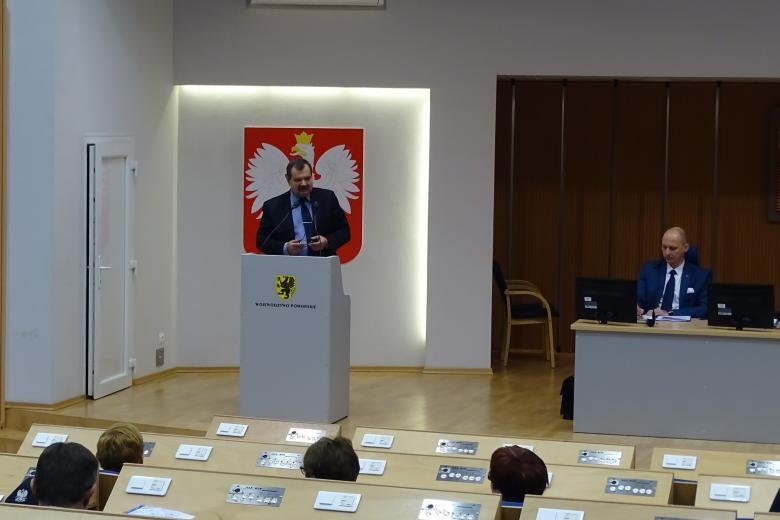 Zdjęcie: mężczyzna przy mownicy, z tyłu - orzeł na czerwonym tle, na mównicy - herb Gdańska