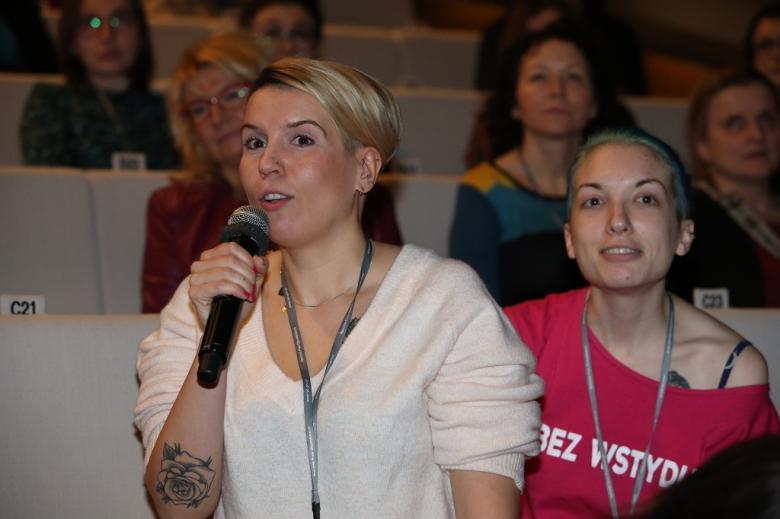 Kobieta w białej bluzce zadaje pytanie