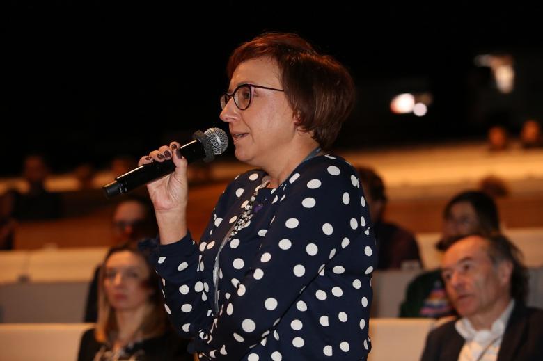 Kobieta w czarno-białej bluzce zadaje pytanie