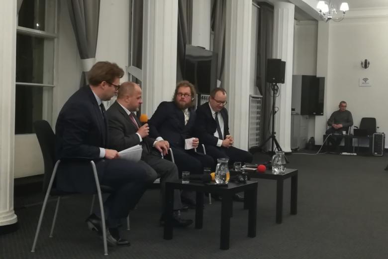 Czterej mężczyźni na krzesłach dla panelistów.