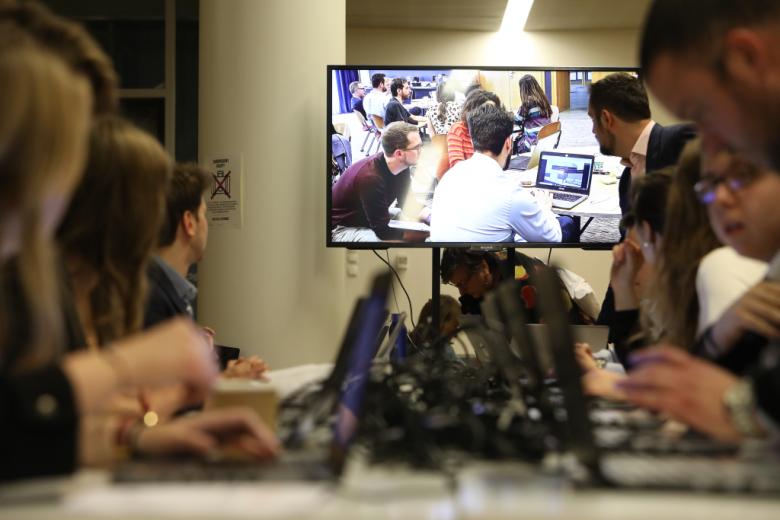 Ludzie przy komputerach, w centrum duży ekran