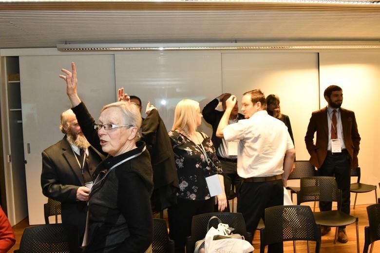 Ludzie na sali podnoszą ręce