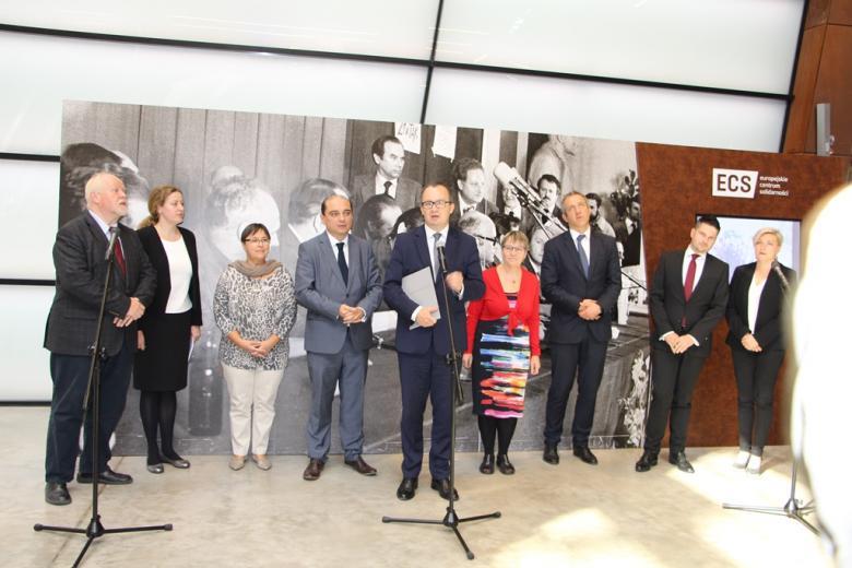 Ludzie stoją przed mikrofonem na tle ściany z dużym historycznym zdjęciem
