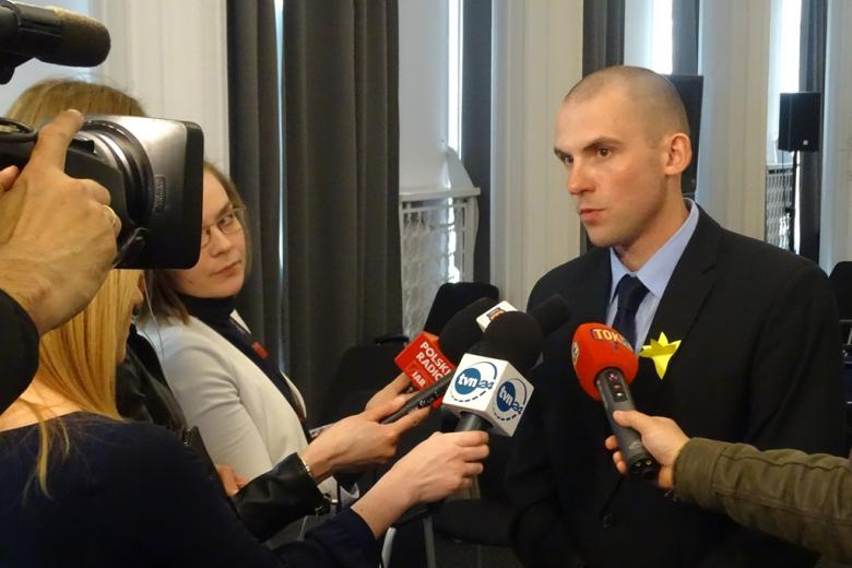 Mężczyzna z żółtym żonkilem rozmawia z dziennikarzami