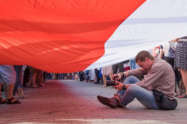 Człowiek w czasie demonstracji - siedzi pod bialo-czerwoną flaga