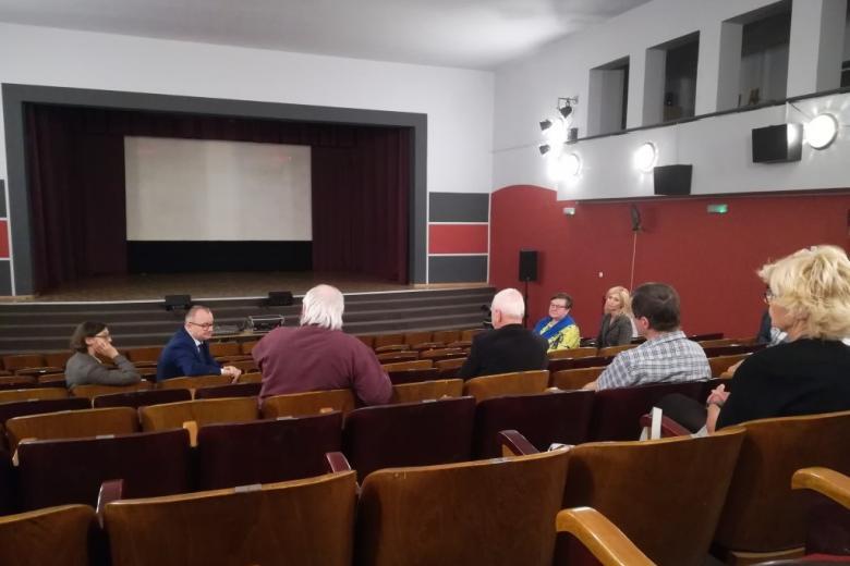 Ludzie siedzą w kinie i rozmawiają