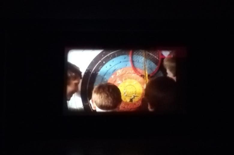 Kadr z filmu na ciemnym tle: dzieci patrzą na tarczę łuczniczą