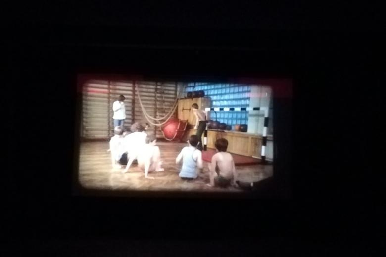 Kadr z filmu na ciemnym tle: dzieci ćwiczą na sali gimnastycznej