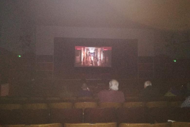 Projekcja filmu w ciemnym kinie -  sylwetki widzów i rozjaśniony ekran