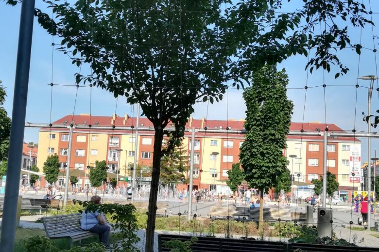 Odnowiony plac w centrum miasta, w głębi dzieci bawią się przy wielkiej fontannie