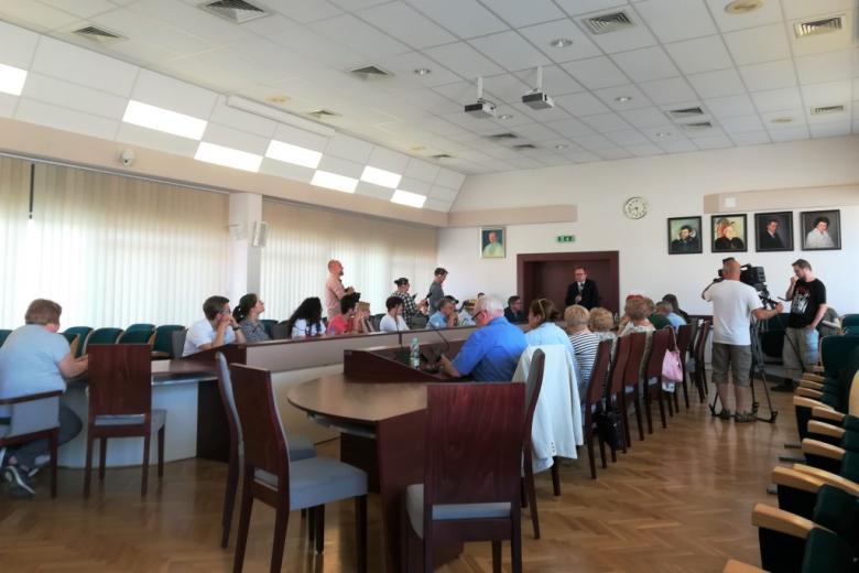 Ludzie przy stole w sali rady, ujęcie z boku