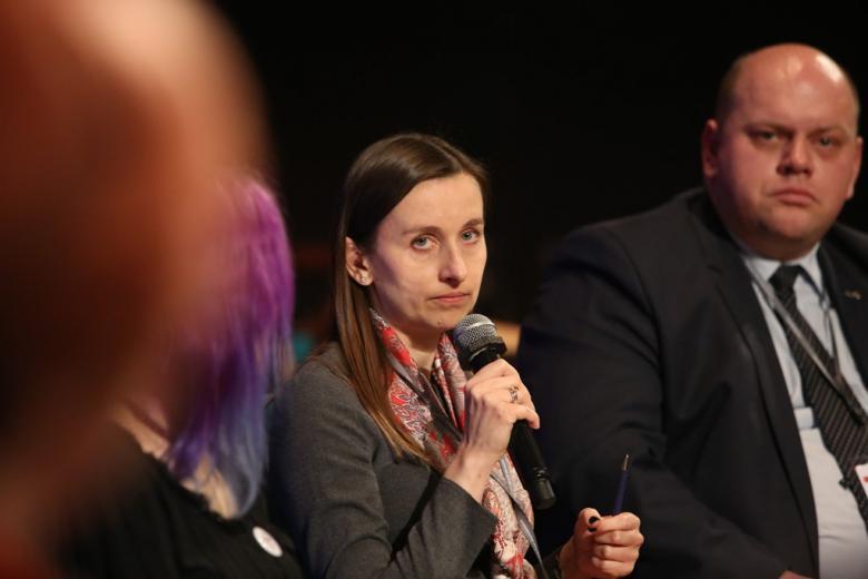 zdjęcie: kobieta mówi do mikrofonu, za nią siedzi mężczyzna