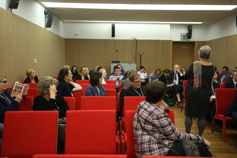 zdjęcie: kilkanaście osób siedzi na sali, pośrodku stoi kobieta