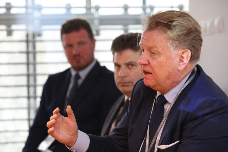 zdjęcie: trzech mężczyzn siedzi i dyskutuje