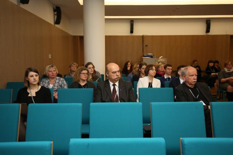 zdjęcie: kilkanaście osób siedzi na turkusowych krzesłach