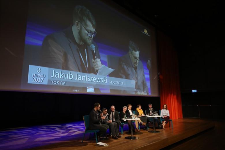 zdjęcie: kilka osob siedzi na scenie, nad nimi duzy ekran