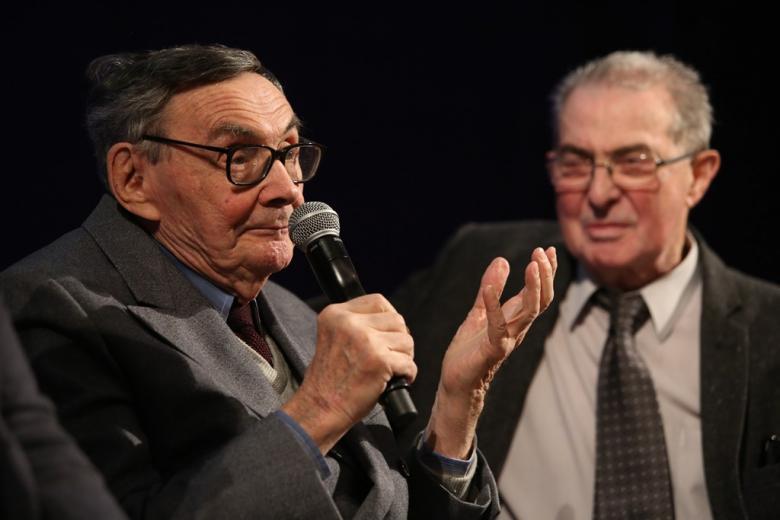 zdjęcie: dwaj starsi mężczyźni, jeden z nich mówi do mikrofonu