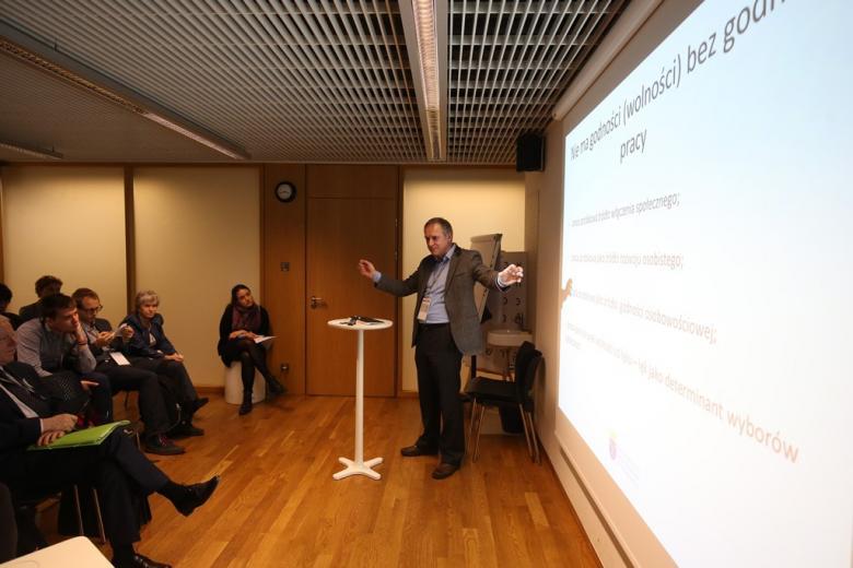zdjęcie: mężczyzna stoi przy ekranie i prezentuje dane
