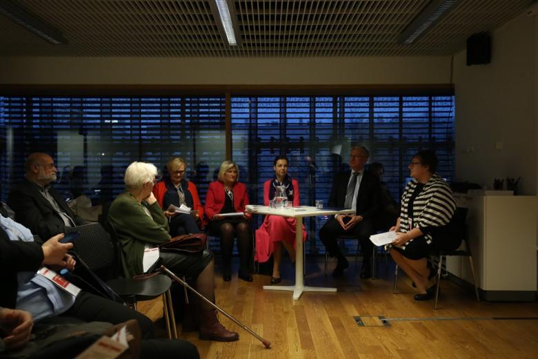 zdjęcie: kilka osób siedzi przy okrągłym stoliku