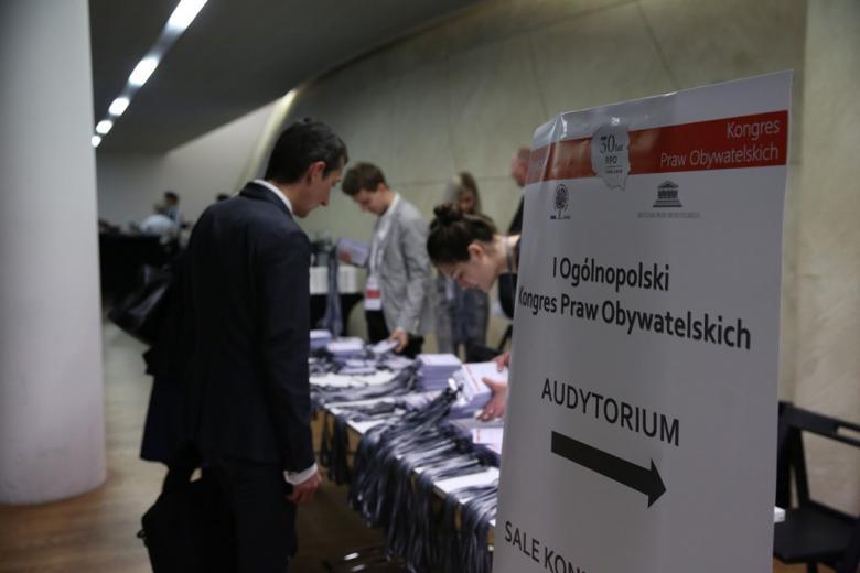 zdjęcie: miejsce gdzie odbywała się rejestracja gości, na stoliku leżą identyfikatory