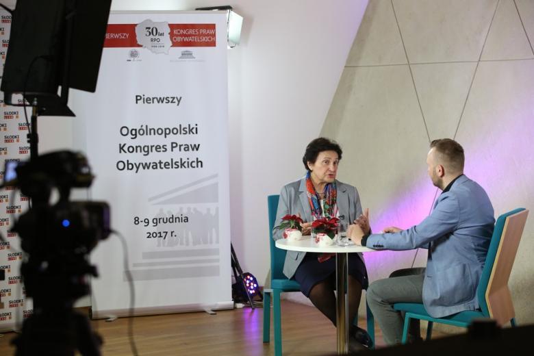 zdjęcie: dwie osoby siedza przy stoliku, za nimi widać baner
