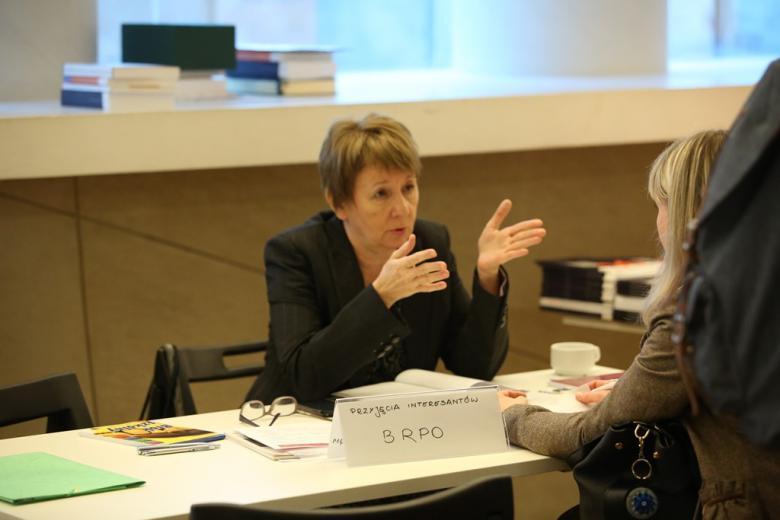 zdjęcie: dwie kobiety siedzą przy stoliku, jedna z nich gestykuluje