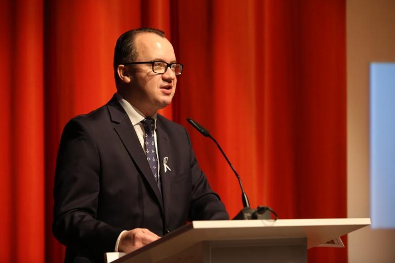 zdjęcie: mężczyzna w garniturze przy mównicy