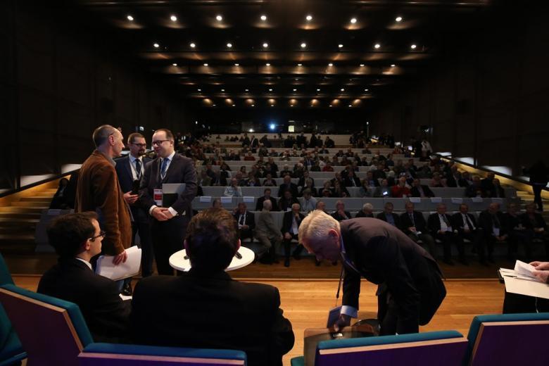 Ludzie na sali plenarnej, drupa osob rozmawia na scenie