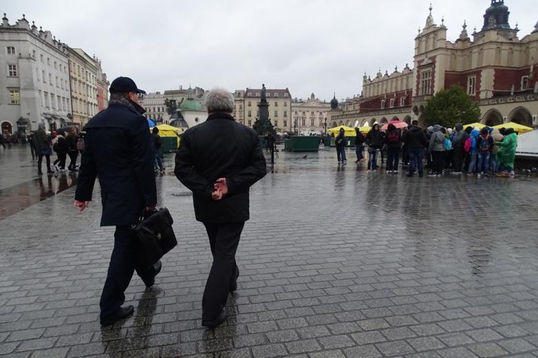 Zdjęcie: dwaj mężczyźni idą w stronę krakowskich Sukiennic