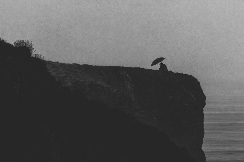 Deszcz, człowiek pod parasolem siedzi blisko stromego brzegu morza