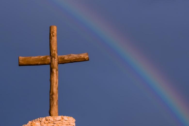 Drewniany krzyż i tęcza na niebie