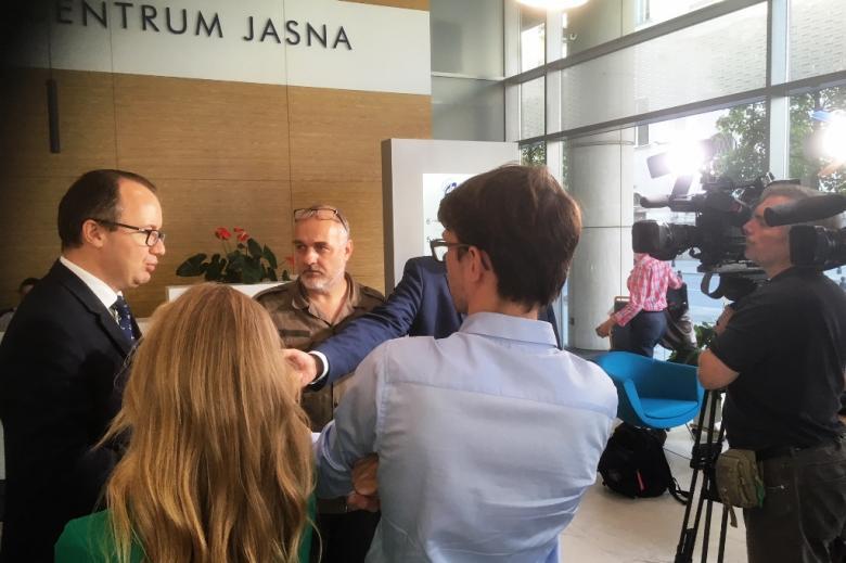 Mężczyzna odpowiada na pytanie dziennikarzy, w tle napis Centrum Jasna