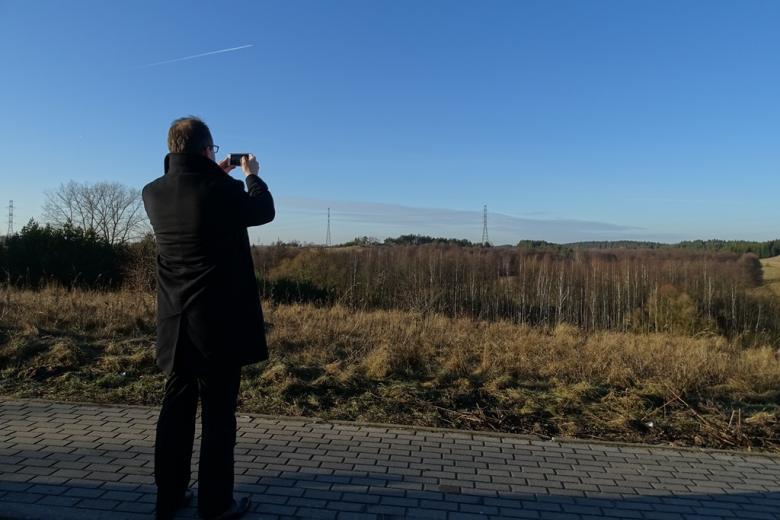 Zdjęcie: mężczyzna fotografuje linię energetyczną przecinająca malowniczą okolicę