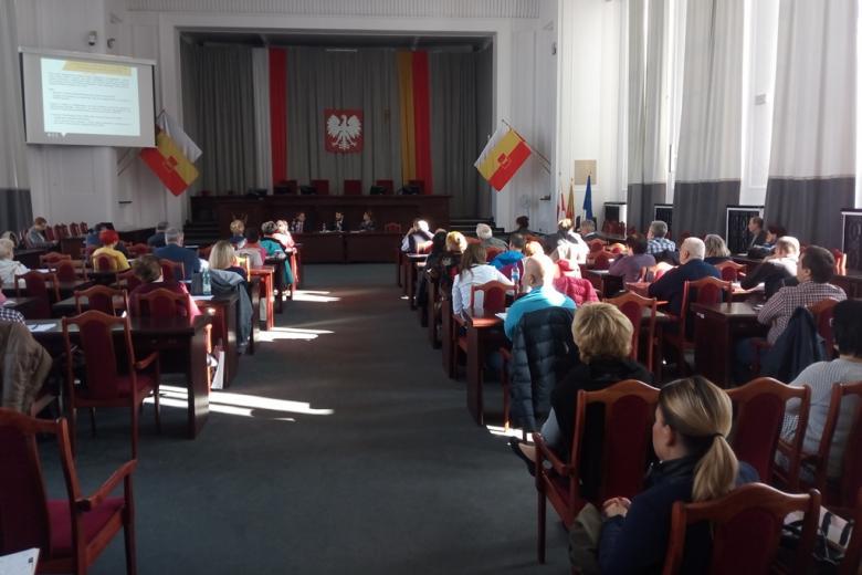 Ludzie na sali posiedzenia władz samorządowych, flaga Łodzi